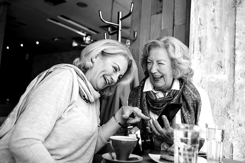 Two senior women sitting in modern cafe and drinking coffee, chatting in relaxed atmosphere, using smart phone