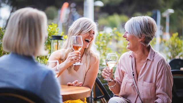 Women enjoying wine and laughing at Hidden Spring of McKinney