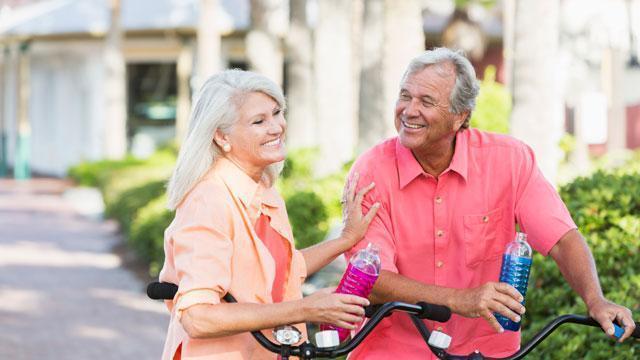 A couple enjoying a bike ride holding water bottles.