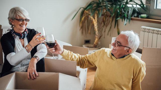 A couple enjoying wine while unpacking boxes.