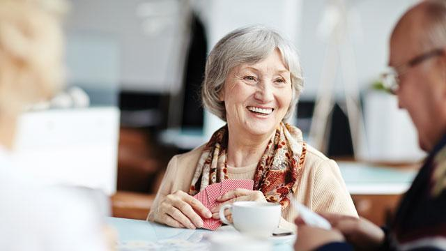 A women enjoying coffee and plaing cards.