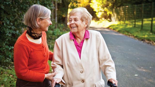 two senior women walking and chatting outdoors