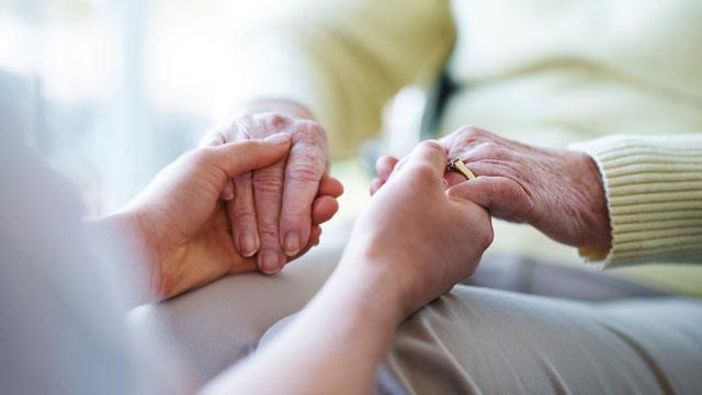 close up of caregiver holding a senior woman's hands