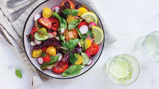 Bowl of salad and a glass of lemon water.