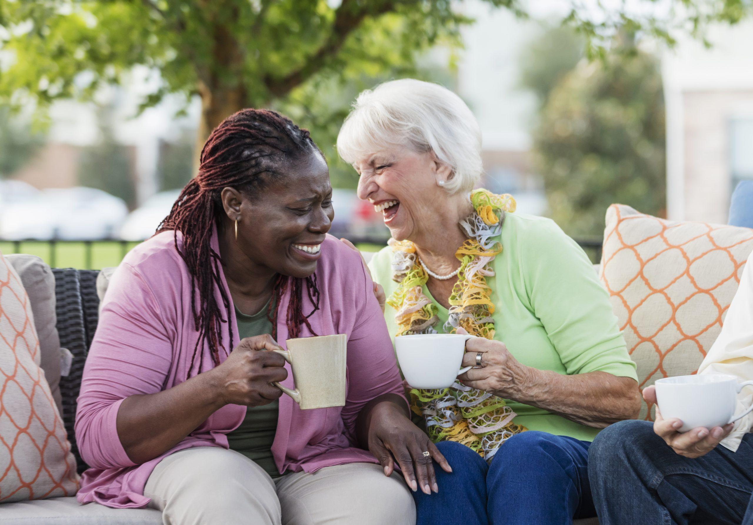 A senior woman in her 70s, drinking coffee and laughing with her African-American friend, a mature woman in her 50s. They are sitting outdoors on a patio sofa.
